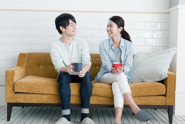 ソファーに座る20代カップルの写真素材 [FYI01439163]
