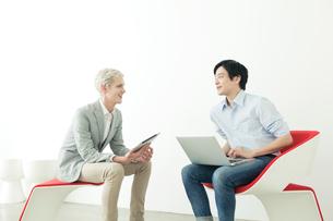 椅子に座り向かい合う20代の日本人男性と外国人男性の写真素材 [FYI01439215]
