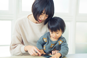 リビングでスマホを操作する親子の写真素材 [FYI01439285]