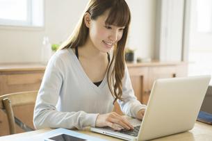 笑顔でパソコンを操作する20代女性の写真素材 [FYI01439319]