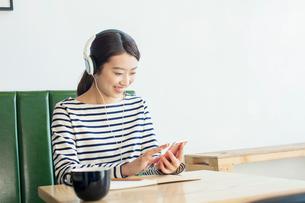 カフェで音楽を聴く20代女性の写真素材 [FYI01439349]