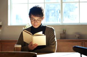 部屋で読書をする20代男性の写真素材 [FYI01439382]