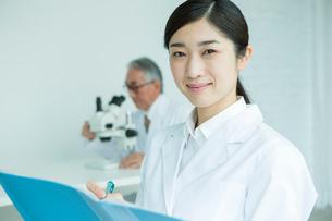 白衣を着た30代女性と顕微鏡を覗く男性の写真素材 [FYI01439405]