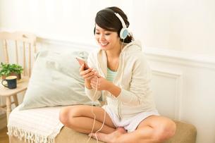 スマホで音楽を聴く笑顔の20代女性の写真素材 [FYI01439415]