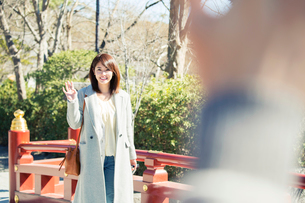 待ち合わせ場所で手を振る20代女性の写真素材 [FYI01439454]