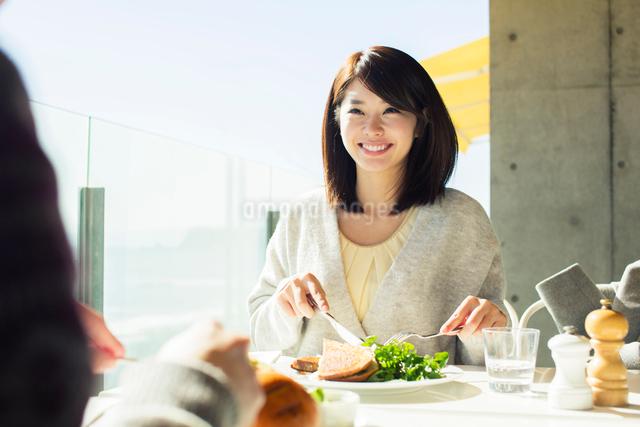 テラス席で食事を楽しむ20代女性の写真素材 [FYI01439480]