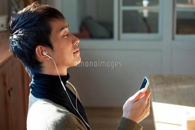 スマホで音楽を聴く20代男性の写真素材 [FYI01439493]