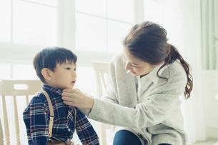 子供のボタンを留める母親の写真素材 [FYI01439498]