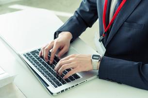 パソコンを使い仕事をするスーツ姿の20代男性手元の写真素材 [FYI01439523]
