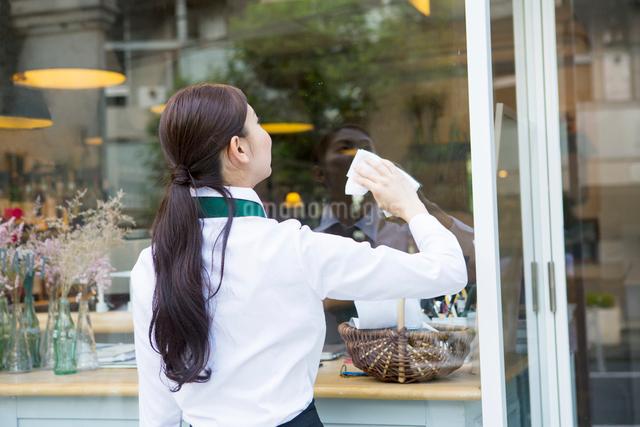 掃除をする20代女性カフェ店員の写真素材 [FYI01439525]