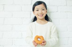 ドーナツを持つ笑顔の女の子の写真素材 [FYI01439547]