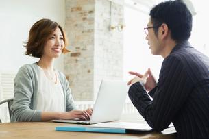男性と会話をする仕事中の20代女性の写真素材 [FYI01439579]