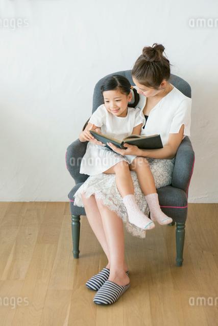 ソファに座り本を読む笑顔の親子の写真素材 [FYI01439617]