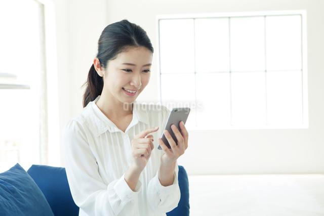 ソファーでスマホを使う20代女性の写真素材 [FYI01439658]