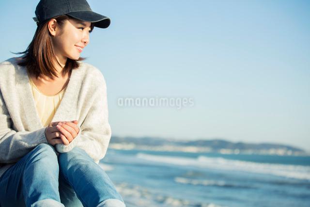 海沿いで海を眺める20代女性の写真素材 [FYI01439925]
