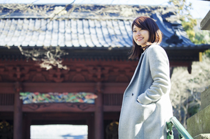 神社を散策する笑顔の20代女性の写真素材 [FYI01439941]