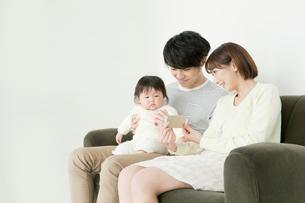ソファでスマホを見せている親子の写真素材 [FYI01440024]