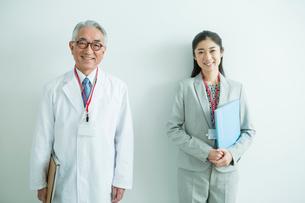 白衣を着た70代男性と会社員女性の写真素材 [FYI01440033]