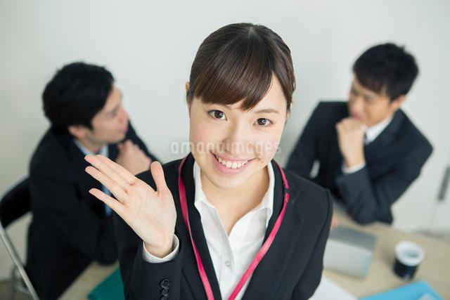 合図をする笑顔のスーツ姿の20代女性の写真素材 [FYI01440067]