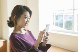 スマホを使う20代女性の写真素材 [FYI01440083]