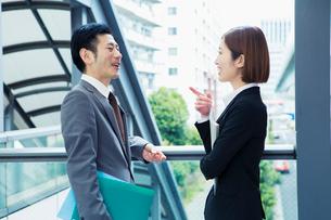 屋外で話すスーツ姿の男女の写真素材 [FYI01440098]