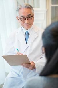 白衣を着た70代男性医師と患者の写真素材 [FYI01440106]