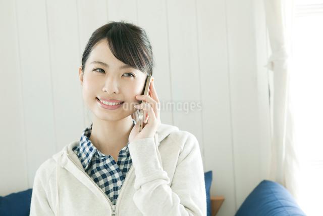ソファに座って電話をする若い女性の写真素材 [FYI01440121]