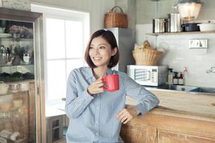 キッチンでカップを持つ20代女性の写真素材 [FYI01440184]