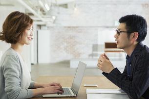 男性と会話をする仕事中の20代女性の写真素材 [FYI01440215]
