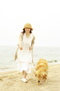 海辺で犬と歩くシニア女性の写真素材 [FYI01440958]