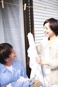 洗濯物を取り込む夫婦の写真素材 [FYI01441086]