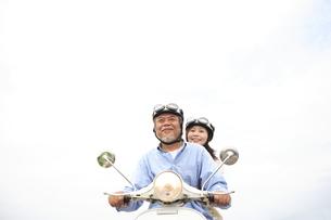 スクーターに乗っているシニア夫婦の写真素材 [FYI01441102]