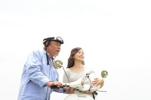 スクーターのそばで談笑するシニア夫婦の写真素材 [FYI01441130]
