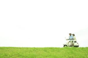 スクーターで草原を走るシニア夫婦の写真素材 [FYI01441307]