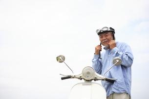 スクーターの横に立っているシニア男性の写真素材 [FYI01441318]