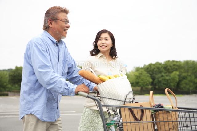 ショッピングカートを押しているシニア夫婦の写真素材 [FYI01441574]