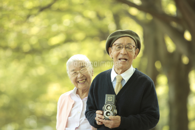 並木道でカメラを持つシニア夫婦の写真素材 [FYI01441959]