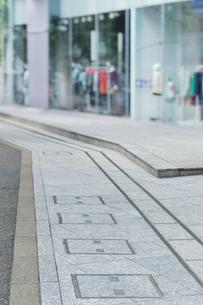 石畳の通路とファッションショップのショーウィンドーの写真素材 [FYI01442460]