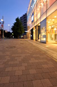 夜明けの石畳の歩道とファッションビルの灯りの写真素材 [FYI01443138]