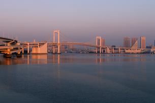 朝日に染まるレインボーブリッジと高層ビルの写真素材 [FYI01443770]