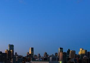 三田のマンションの階上から見る夕日に輝く高層ビル群の写真素材 [FYI01444480]