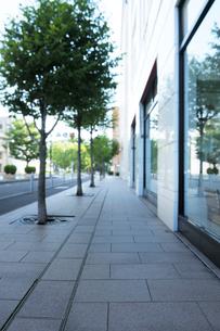 早朝の歩道とビルの壁面の写真素材 [FYI01444525]