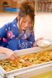 金魚すくいをする浴衣の女性の写真素材 [FYI01445985]