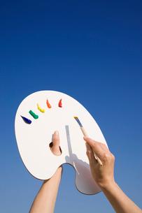 パレットと筆を持つ女性の手 青空の写真素材 [FYI01446310]