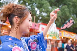 金魚の袋を持つ浴衣の女性の写真素材 [FYI01446448]