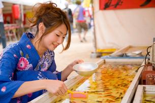金魚すくいをする浴衣の女性の写真素材 [FYI01446719]