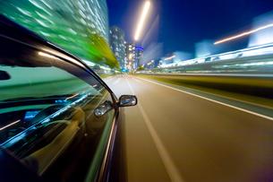 流れる夜景の自動車とサイドミラーと運転席の写真素材 [FYI01450815]