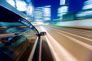 流れる夜景の自動車とサイドミラーと運転席の写真素材 [FYI01451102]