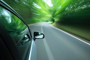 新緑の道を走るハイブリッドカーの写真素材 [FYI01451298]
