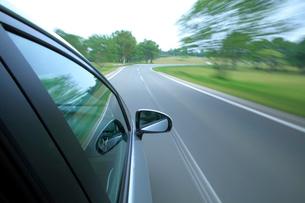 新緑の道を走るハイブリッドカーの写真素材 [FYI01451376]